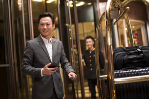 Cheerful Chinese businessman in hotel lobbyの写真素材 [FYI02232069]