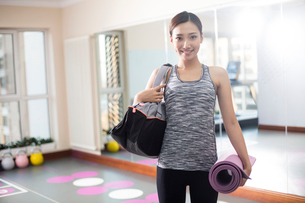 Young woman with yoga mat at gymの写真素材 [FYI02232074]