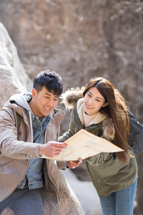 Happy young Chinese couple looking at a map outdoorsの写真素材 [FYI02232115]