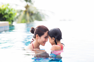 Happy Chinese mother and daughter having fun in swimming poolの写真素材 [FYI02232122]