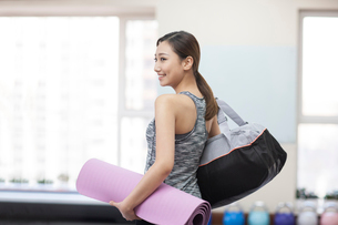 Young woman with yoga mat at gymの写真素材 [FYI02232148]