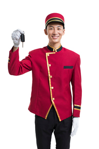 Young Chinese bellboy holding a car keyの写真素材 [FYI02232151]