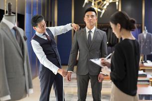 Chinese fashion designer taking measurement of customerの写真素材 [FYI02232169]