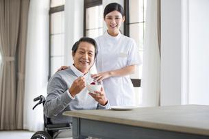 Nursing assistant taking care of senior man in wheel chairの写真素材 [FYI02232171]