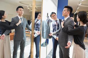 Chinese fashion designers examining suit on customerの写真素材 [FYI02232188]