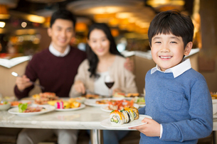 Cheerful young Chinese family having buffet dinnerの写真素材 [FYI02232195]