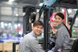Confident workers driving forklift in the factoryの写真素材 [FYI02232197]