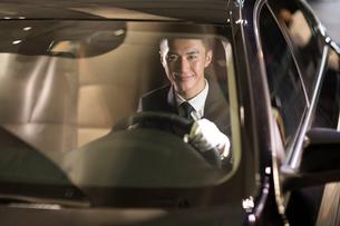 Cheerful Chinese chauffeur driving carの写真素材 [FYI02232203]