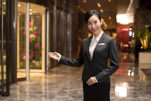 Confident Chinese hotel receptionist greetingの写真素材 [FYI02232220]