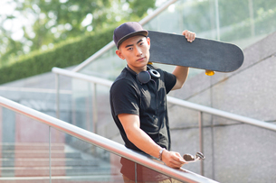 Young Chinese man with headphones carrying a skateboard on his shoulderの写真素材 [FYI02232221]