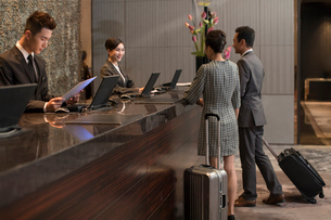 Chinese couple checking into hotelの写真素材 [FYI02232230]