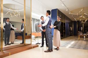 Chinese fashion designers examining suit on customerの写真素材 [FYI02232231]