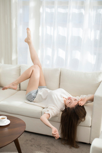 Cheerful young Chinese woman relaxing on sofaの写真素材 [FYI02232234]