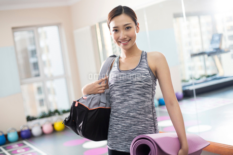 Young woman with yoga mat at gymの写真素材 [FYI02232245]