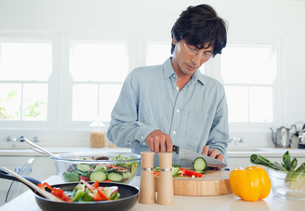 A man cuts a cucumber to add to a salad in the kitchenの写真素材 [FYI02232308]