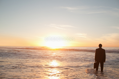 Businessman standing in the water while holding a briefcaseの写真素材 [FYI02232364]