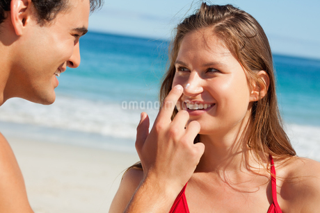 Man putting some sunscreen on his girlfriends noseの写真素材 [FYI02232464]