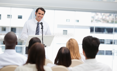 Black haired businessman smiling as he is being watched by an audienceの写真素材 [FYI02232572]
