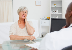 Mature woman telling her doctor about her neck painの写真素材 [FYI02232647]