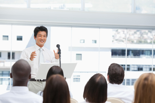 Businessman smiling as he gestures to an audience who are watching himの写真素材 [FYI02232703]