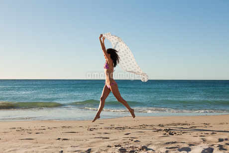 Attractive woman in bikini jumping with a sarongの写真素材 [FYI02232774]