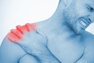 Man wincing in pain at shoulder painの写真素材 [FYI02232785]