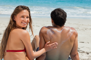 Portrait of a woman applying sunscreen in form of heart on her boyfriendの写真素材 [FYI02232948]