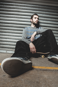 Skater sitting on his board taking a breakの写真素材 [FYI02233067]