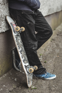 Skater leaning against wall with his boardの写真素材 [FYI02233133]