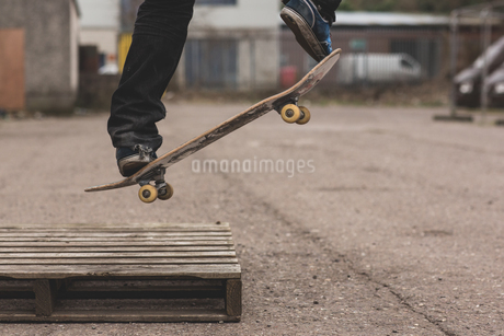 Skater doing ollie off wooden crateの写真素材 [FYI02233158]