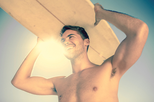 Handsome man holding his surfboard above his headの写真素材 [FYI02233183]