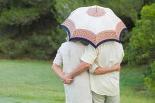 Couple embracing under a parasolの写真素材 [FYI02233185]