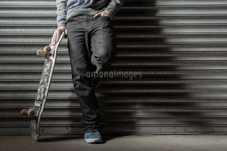 Skater leaning against metal shuttersの写真素材 [FYI02233214]