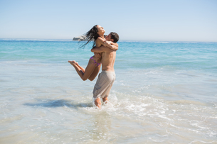 Handsome man holding his girlfriend in the seaの写真素材 [FYI02233347]