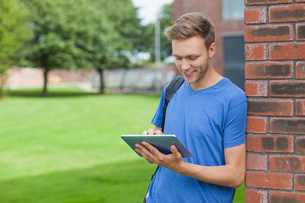 Smiling handsome student leaning against wall using tabletの写真素材 [FYI02233469]