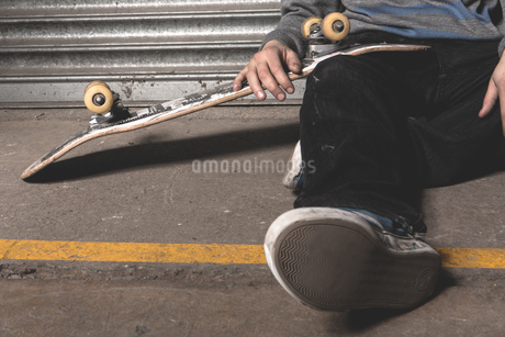 Skater sitting on ground with boardの写真素材 [FYI02233559]