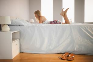 Woman lying on bed with flip flops on the floor besideの写真素材 [FYI02233608]