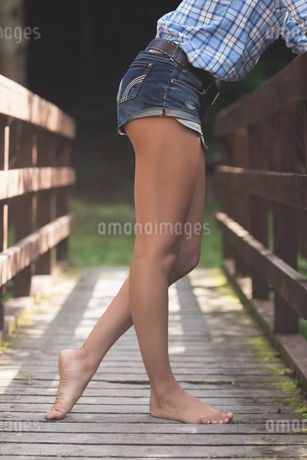 Side view of lower body of model leaning against bridgeの写真素材 [FYI02233622]