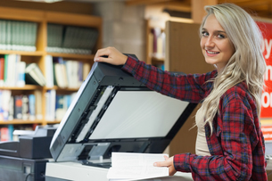 Pretty blonde student using photocopierの写真素材 [FYI02233741]