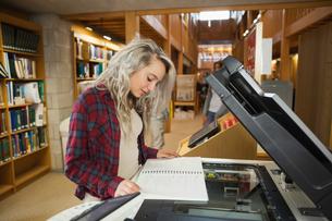 Focused blonde student standing next to photocopierの写真素材 [FYI02233795]