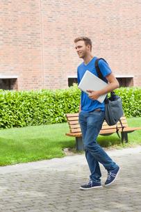 Happy handsome student carrying laptopの写真素材 [FYI02233857]
