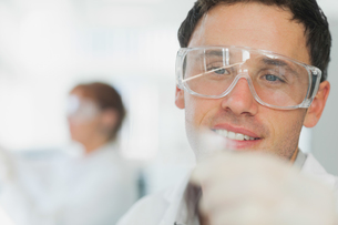 Handsome young scientist looking at microscope slideの写真素材 [FYI02233868]
