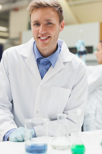 Cheerful handsome student in lab coat looking at cameraの写真素材 [FYI02233910]