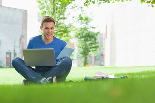 Smiling handsome student sitting under tree studyingの写真素材 [FYI02233947]