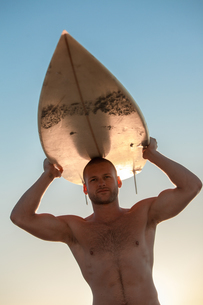 Handsome surfer holding his surfboardの写真素材 [FYI02233966]