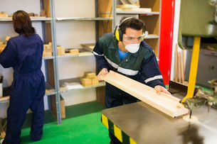 Focused craftsman wearing safety protection using sawの写真素材 [FYI02233986]