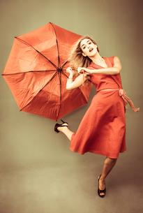 Beautiful woman posing with a broken umbrellaの写真素材 [FYI02234015]