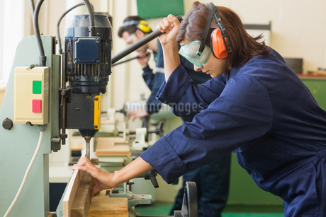 Trainee with safety glasses drilling woodの写真素材 [FYI02234047]