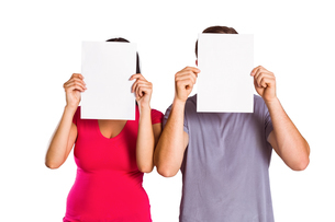 Couple covering faces with paperの写真素材 [FYI02234182]