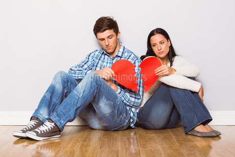 Young couple sitting on floor with broken heartの写真素材 [FYI02234192]